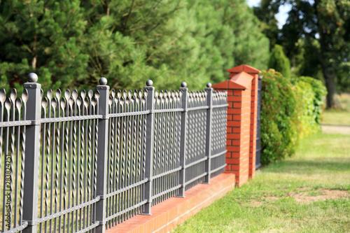Ogrodzenia, metalowe ogrodzenie ze stalowych prętów i czerwonej cegły, zielone drzewa. - fototapety na wymiar