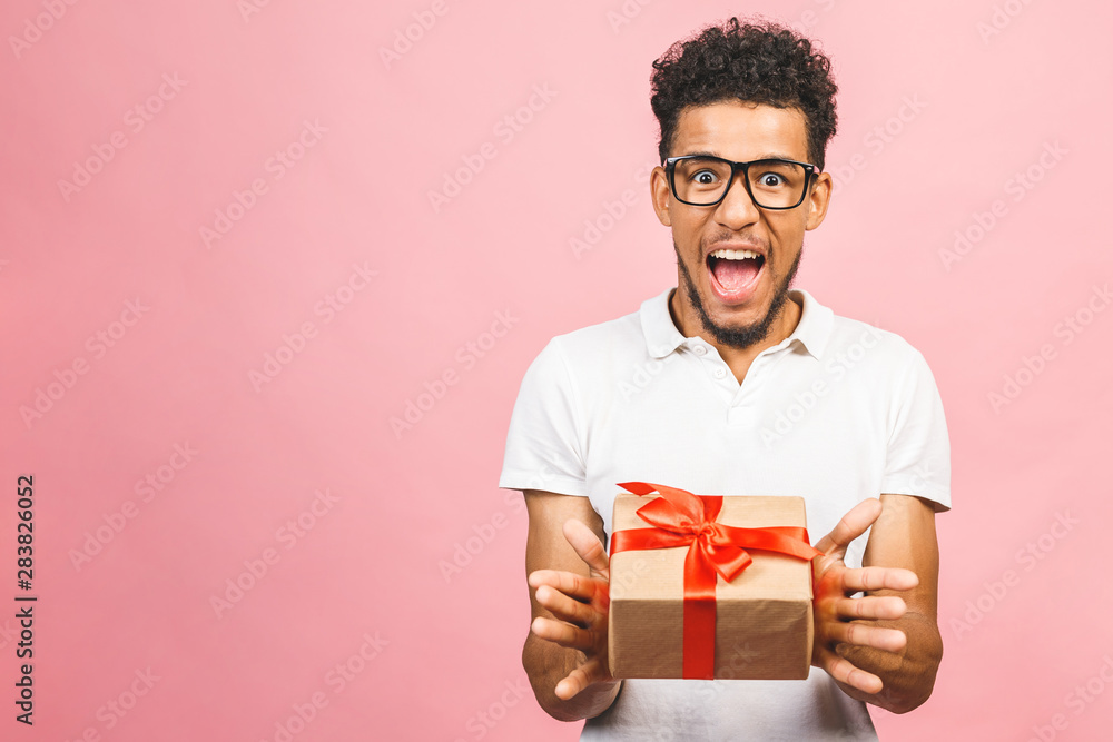 Fototapety, obrazy: Cheerful smiling african american millennial guy in eyewear holding wrapped present box. Happy black young man congratulating, giving birthday gift, isolated on pink background.