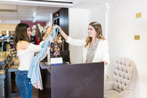 Customer Buying Garments From Clerk At Counter Poster Mural XXL