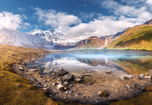 Beautiful Lake With Fog In Mountain Valley At Sunrise In Autumn. Landscape With Snowy Manaslu Mountain, Stones, Yellow Grass, Green Hills, Blue Sky With Clouds, Reflection In Water In Nepal. Nature