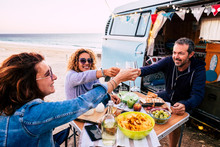 Happy People Group Of Friends Toasting And Enjoying The Travel Vacation Together - Cheerful. Womanandman With Food In Outdoor Leisure Activity - Old Vintage Van And Ocean In Background