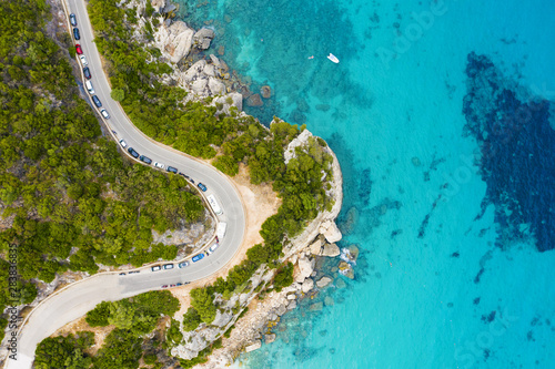 Obraz na plátně  View from above, stunning aerial view of a road that runs along a rocky coast bathed by a turquoise and transparent sea