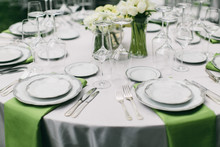Wedding Reception Table Setting, Fine China Plates, Green Napkin Hanging Off Table, Silverware, Wine Glasses, And Flower Arrangments
