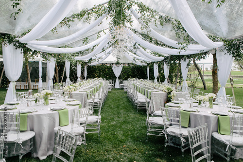 Obraz Outdoor summer wedding tent decorated with hanging fabric, greenery, and crystal chandeliers, wedding reception tables, green accent color - fototapety do salonu