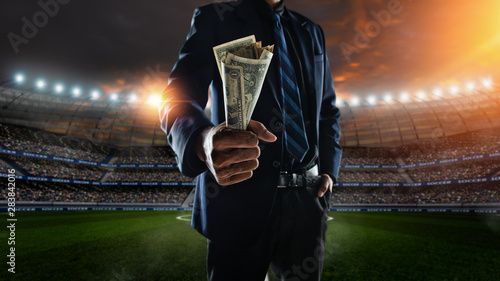 Photo businessman holding large amount of bills at Soccer stadium in background
