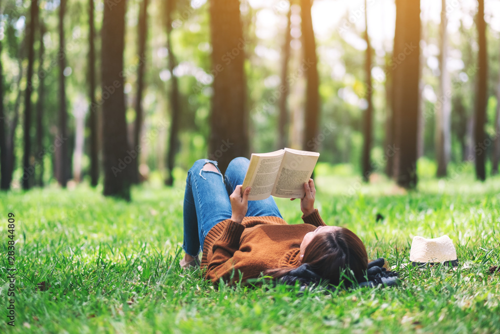 Fototapeta A beautiful Asian woman lying and reading a book in the park
