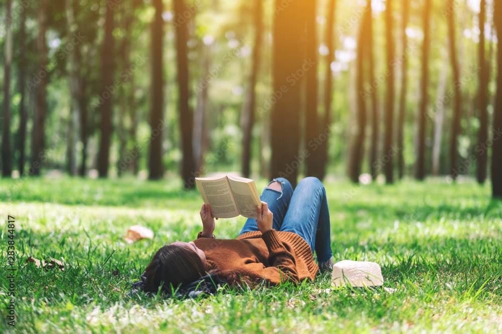 Fototapety, obrazy: A beautiful Asian woman lying and reading a book in the park