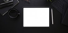 Top View Of Blank Screen Tablet On Black Desk Background
