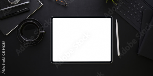 Fotografia  Top view of blank screen tablet on black desk background