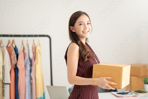 Fotomural  woman fashion designer standing and holding cardboard box.