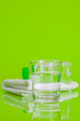 Leinwandbild Motiv Glass cup of mineral water on green background