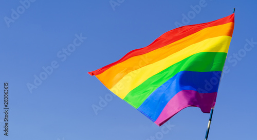 Poster de jardin Montagne Gay rainbow flag waving in the wind in a clear blue sky