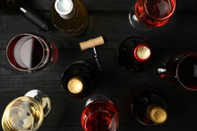 Bottles And Glasses With Different Wine On Wooden Background, Top View