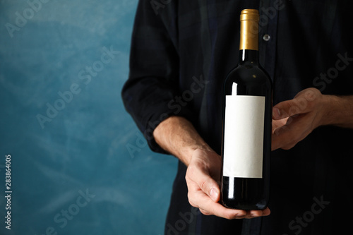 Fotomural  Man in shirt hold bottle of wine with empty space against blue background