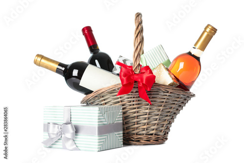 Foto Wicker basket with bottles of wine and presents isolated on white background