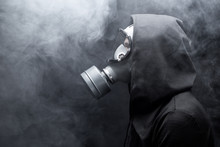 A Man In A Gas Mask In The Abstract Smoke. Black Background.  Copy Space.