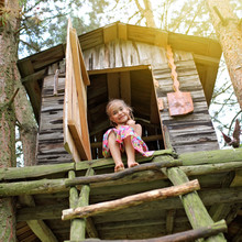 Happy Cute Kid Playing In The Treehouse