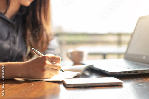 Business woman using laptop and writing on a notepad with a pen at a coffee shop. Working on project concept