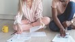 Young multi-ethnic couple sit at kitchen floor, make calculations, surrounded with paper sheets. Planning concept