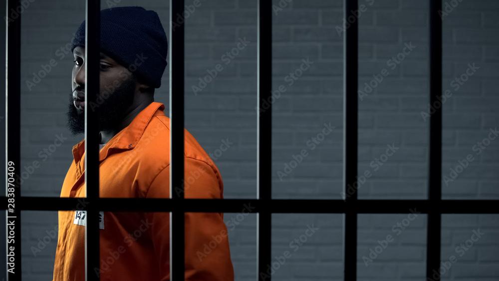 Fototapeta Afro-american criminal in jail cell serving sentence, punishment for kidnapping