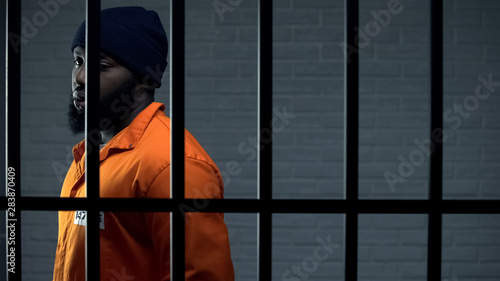 Fotomural Afro-american criminal in jail cell serving sentence, punishment for kidnapping
