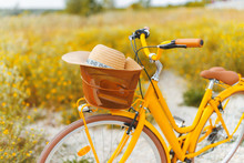 Vintage Travel Concept. Photo Of A Yellow Bicycle With Hat In Basket, Standing In Field