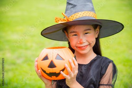 Fényképezés  Little asian girl in witch costume celebrate Halloween outdoor ,holding pumpkin bucket and smiles
