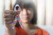 canvas print picture - Autistic child girl holding ribbon symbol of colorful pieces of jigsaw together for day of raise awareness about people with Autism Spectrum Disorder throughout the world.