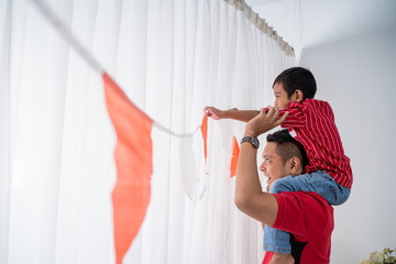 family decorating their home with indonesian flag for independence day