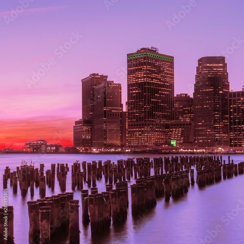 Sticker - View from the water of the bay on the night city center of New York at sunset. Skyscrapers glowing in the dark against the sunset sky.