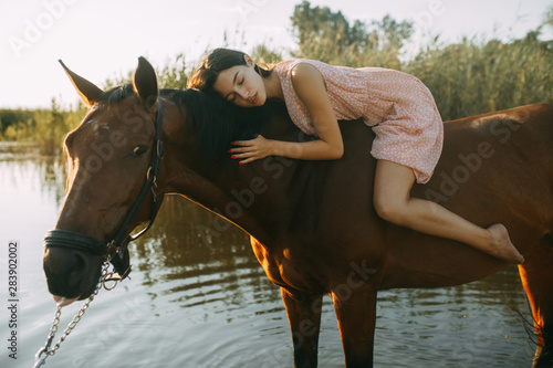 Woman lies astride a horse at river. Canvas Print