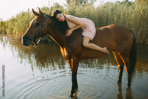 Woman lies astride a horse at river. Wallpaper Mural