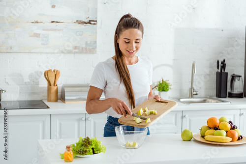 happy young woman putting sliced green apple in bowl Fototapeta