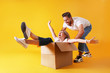 canvas print picture - Young married couple moving into a new home. Attractive blonde woman sitting in cardboard box while bearded man pushes her. Newely weds fooling around. Isolated yellow background, copy space, close up