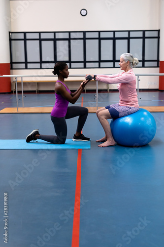 obraz PCV Trainer assisting disabled senior woman to exercise with dumbbell in sports center