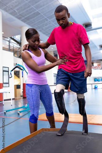 Female physiotherapist helping disabled man walk with prosthetic leg on ramp in sports center