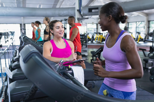 Female trainer interacting with woman in fitness center