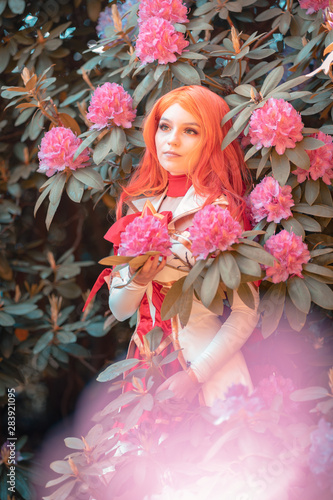 Photo young red head girl play cosplay miss fortune from leaque of legends in front of flowers