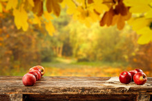 Red Apples On Wooden Table Top With Autumn Background. Empty Space For Decoration And Products.