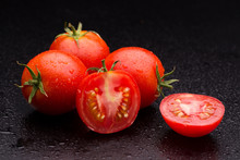 Sliced Tomato On A Dark Background. Tomatoes Close-up. Tomatoes Covered With Drops Of Water.
