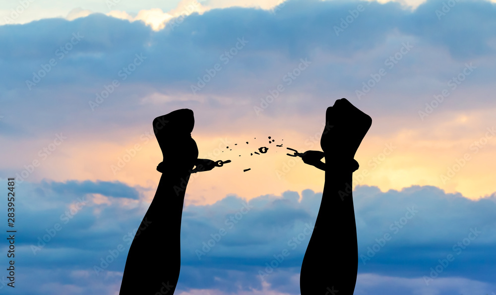 Fototapeta Silhouette of hands in handcuffs with sunset background