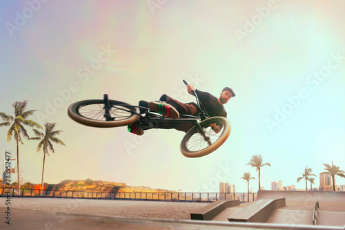 BMX rider is performing tricks in skatepark on sunset. Fototapet