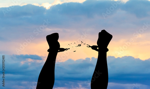 Canvas Print Silhouette of hands in handcuffs with sunset background