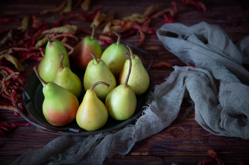 Pears on a tray and colorful dried leaves. Autumn arrangement of fall harvest on brown wooden background.