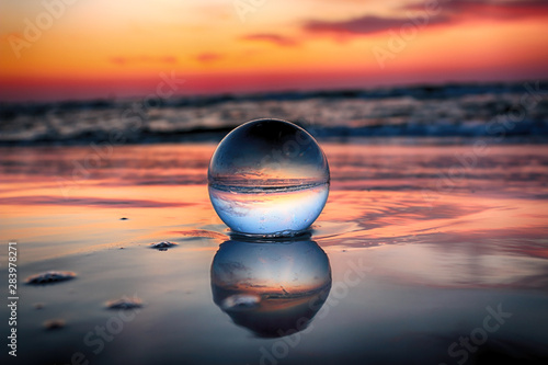 Gris traffic Beautiful sunset on the beach in Slowinski National Park near Leba, Poland. View of a starfish through a glass, crystal ball (lensball) for refraction photography. Wild, untouched nature.