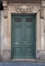 Classical Architecture Columns And Stone Relief Decorations Above Wooden Framed Door Painted In Green Color With Brass Handles. Rectangle Shape Entrance Of Retro Building In Paris France.