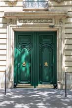Old Wooden Door. Entrance With Double Door Painted In Bright Green Color. Elegant Doorway Of White Stone Building In Paris France. Green Wooden Door Panels With Ornate Golden Metal Door Knockers.