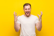 Handsome man over yellow background unhappy and frustrated with something