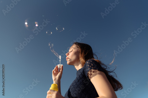 Fotografie, Obraz Beautiful young brunette girl blowing soap bubbles into the sky.