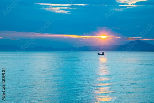 Foto auf Leinwand Blau Jeans Fishing boat on sea in sunset lights in Sanya, Hainan, China